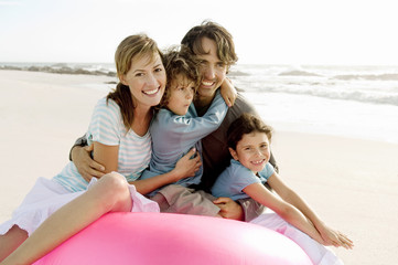 Parents and two children sitting on the beach, posing for the camera, outdoors