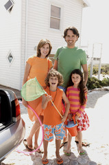 Parents and two children in front of a house, holding beach accessories, outdoors