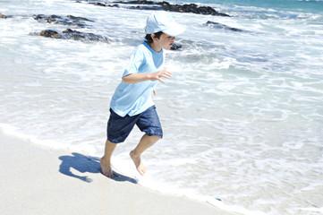 Boy running on the beach, outdoors
