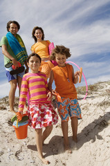 Parents and two children walking on the beach, outdoors
