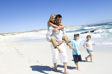 Parents and two children walking on the beach, man carrying woman on his back, outdoors