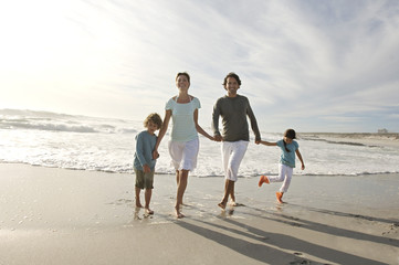 Couple, son and daughter walking on the beach, outdoors
