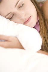 Portrait of a young woman lying, sleeping, indoors