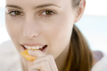 Portrait of a young woman eating a piece of melon, indoors