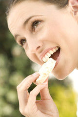 Portrait of a young woman eating a biscuit, outdoors