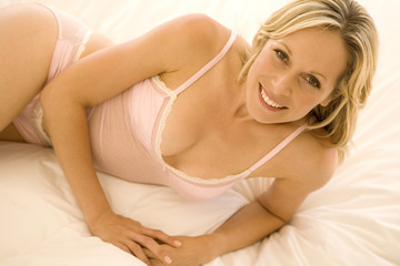 Young smiling woman lying on bed
