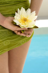 Young woman holding a water lily, pool, outdoors