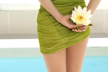 Young woman near a pool, holding a water lily, outdoors