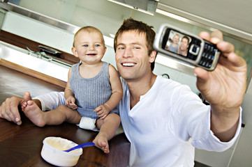 Young man with baby, using camera phone