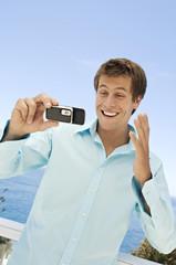 Portrait of a man using camera phone