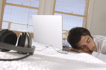 Young man sleeping in front of laptop