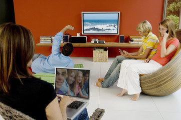 Family in living room, woman using laptop, man watching TV, 2 teens using mobile phone