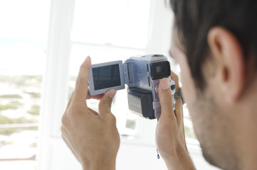 Young man using camcorder