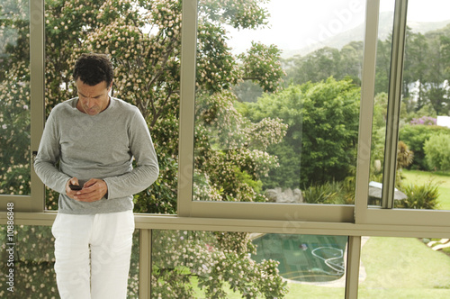 Man leaning against bay window, using mobile phone