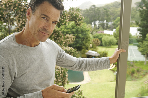 Man leaning against bay window, holding mobile phone