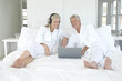 Couple in bathrobe using laptop in bed