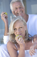 Smiling couple eating apples