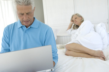 Couple in bedroom, man using laptop, woman lying in background