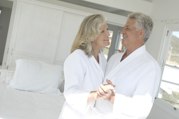 Smiling couple in bathrobe embracing inbedroom
