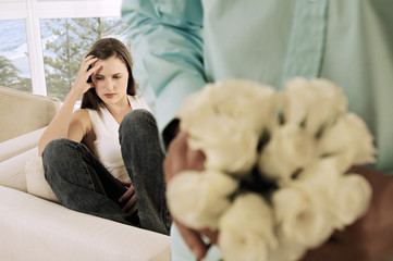Man hiding bunch of flowers behind his back, facing sulking woman