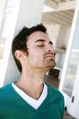 Portrait of a young man with eyes closed, leaning against terrace beam