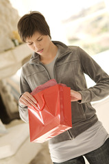 Young woman opening bag, looking disappointed