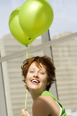 Portrait of young woman holding green balloons