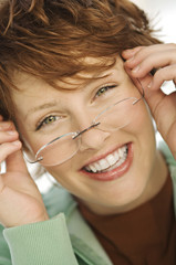 Portrait of young smiling woman putting her eye glasses on