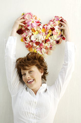 Portrait of young smiling woman holding flowers petals in heart shape