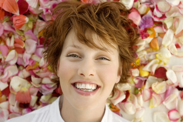 Portrait of young smiling woman, lying on flowers petals
