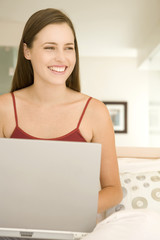 Young woman smiling using a laptop