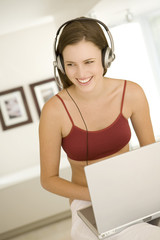 Young woman smiling, listening to music with headphones, laptop on her knees