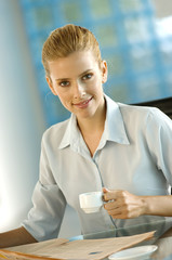 Businesswoman holding coffee cup, portrait