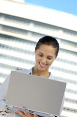 Businesswoman using laptop, smiling