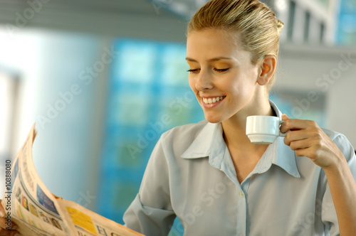 Businesswoman reading newspaper, smiling