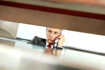 Mature businessman holding telephone receiver