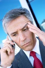 Mature businessman using mobile phone, close-up