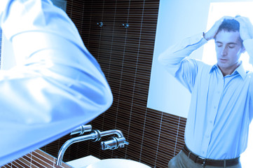 Reflection of mid adult man standing in front of mirror in washroom