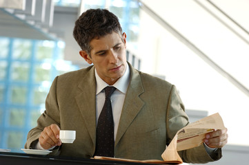 Mid adult businessman reading newspaper