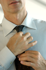 Young businessman adjusting tie, close-up