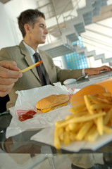 Mid adult businessman having burger and French fries, using laptop