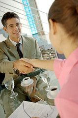 Businessman shaking hand with woman in office