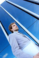 Young businessman holding file by office building, low angle view