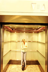 Businesswoman standing in elevator with folded arms