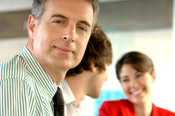 Mature businessman in office, smiling