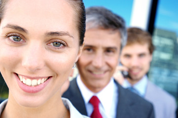 Business people in row, smiling, portrait