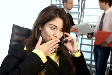 Businesswoman using mobile phone with colleagues standing in background