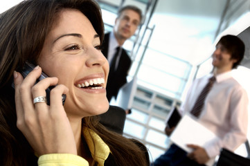 Businesswoman using mobile phone with colleagues in background