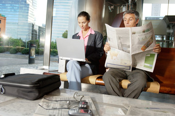 Businesswoman using laptop while businessman reading newspaper