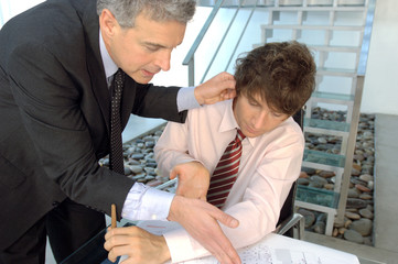 Businessman holding ear of employee in office